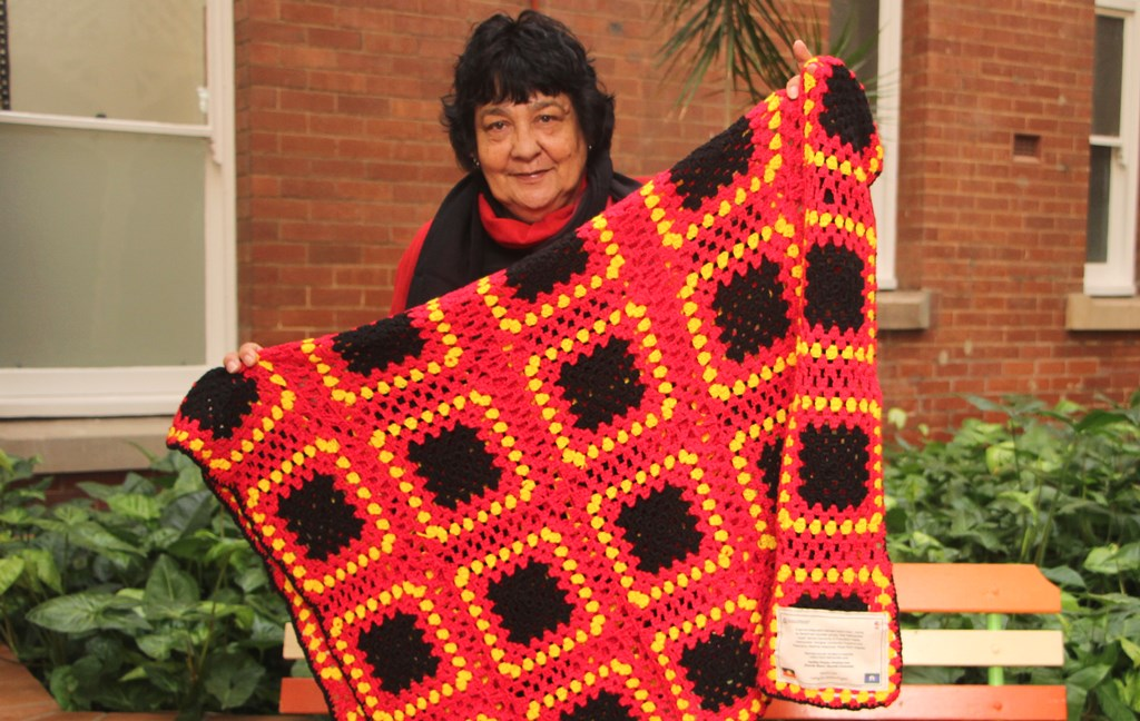 Photograph of Ursula Swan with a quilt